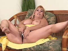 Curvaceous, blonde mature, Joclyn Stone is using a glass dildo to drill her puristic pussy